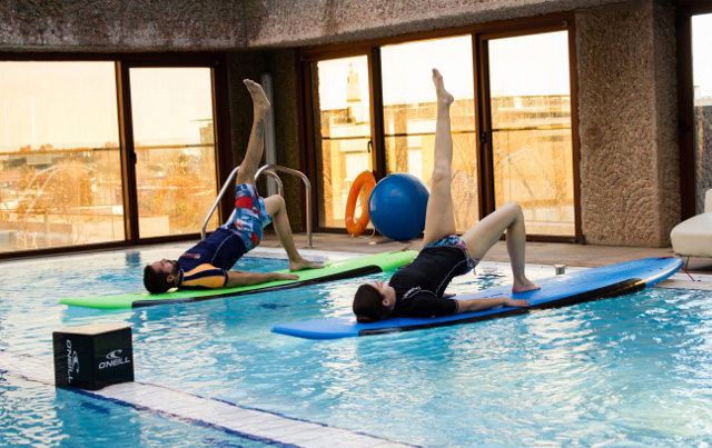 Clase de 'stand up paddle yoga' en piscina